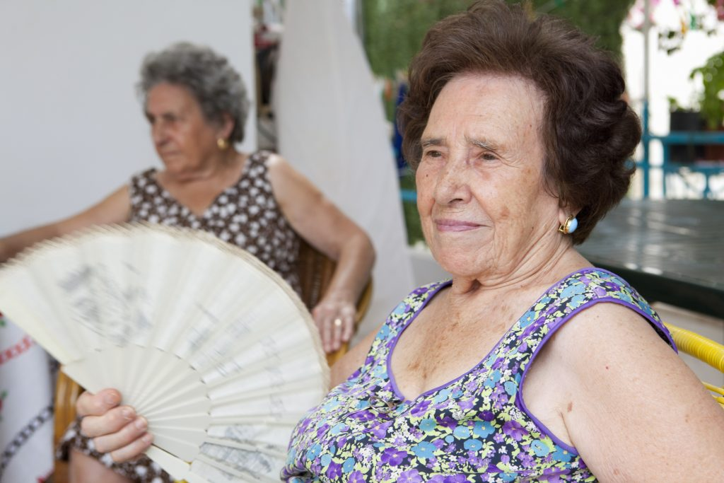 women using a fan to cool down in the summer heat