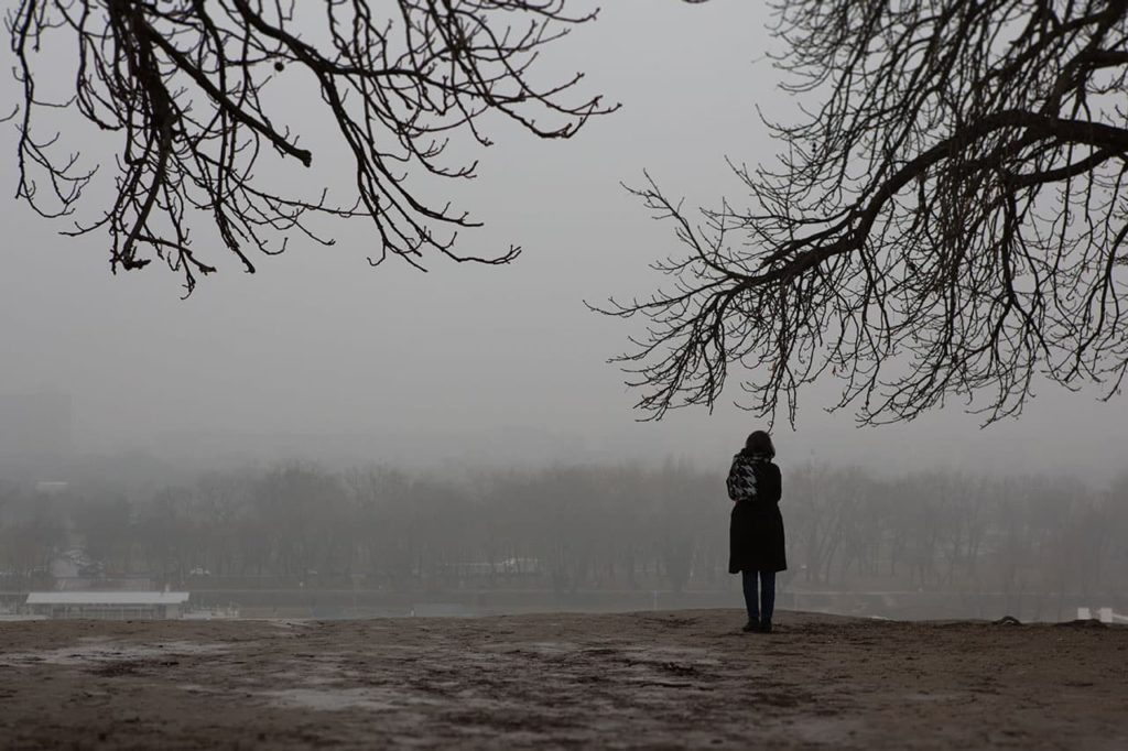 woman standing on river bank on a cold foggy day